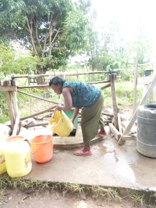 Pastor Patrick's wife, Lucy, Drawing water.